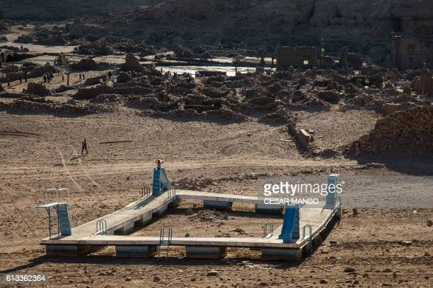 A normally floating platform with slides lies on the parched earth as people walk through the remains of the former town of Mansilla on October 8...