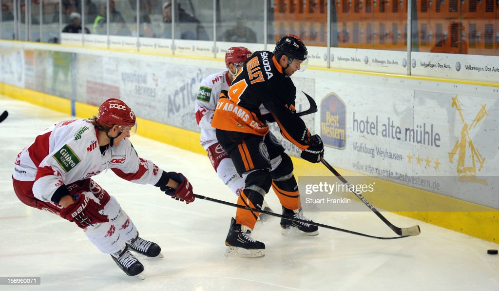 Norman Milley of Wolfsburg challenges for the puck with <a gi-track='captionPersonalityLinkClicked' href=/galleries/search?phrase=Felix+Schuetz&family=editorial&specificpeople=670468 ng-click='$event.stopPropagation()'>Felix Schuetz</a> of Cologne during the DEL match between Grizzly Adams Wolfsburg and Kolner Haie at the Volksbank BraWo Eisarena on January 4, 2013 in Wolfsburg, Germany