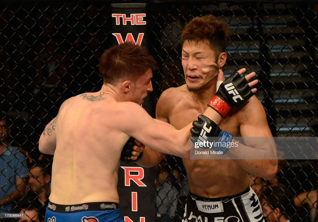 Norman Parke punches Kazuki Tokudome in their lightweight fight during the UFC 162 event inside the MGM Grand Garden Arena on July 6, 2013 in Las Vegas, Nevada.