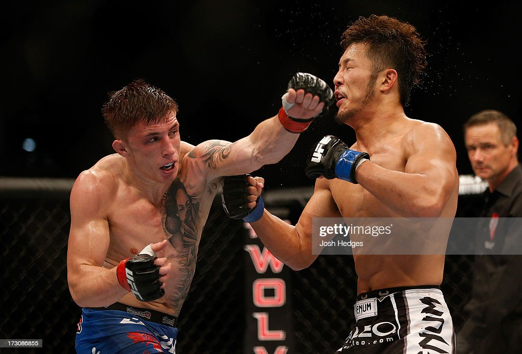Norman Parke (left) punches Kazuki Tokudome in their lightweight fight during the UFC 162 event inside the MGM Grand Garden Arena on July 6, 2013 in Las Vegas, Nevada.