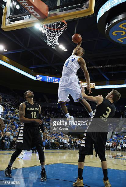 Norman Powell of the UCLA Bruins dunks between Duke Mondy and Travis Bader of the Oakland Golden Grizzlies in the second half at Pauley Pavilion on...