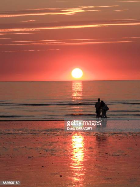 Normandy, couple with dog in the background looking at the sunset on a beach