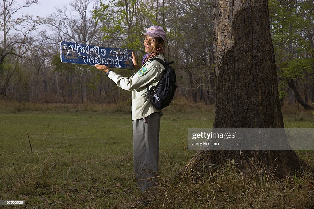 Norng Deng holds up a sign asking villagers to protect rare birds by not cutting grass or fishing in the trapeang behind him The sign had been...