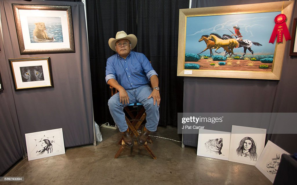 Norris Chee, a Navajo, sits in his booth at the Red Earth Native American Festival, Friday, June 10, 2016 in Oklahoma City, waiting to sell his art work.