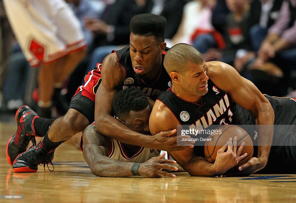 Norris Cole #30 (L) and Shane Battier #31 of the Miami Heat battle for a loose ball with Nate Robinson #2 of the Chicago Bulls in Game Four of the Eastern Conference Semifinals during the 2013 NBA Playoffs at the United Center on May 13, 2013 in Chicago, Illinois.