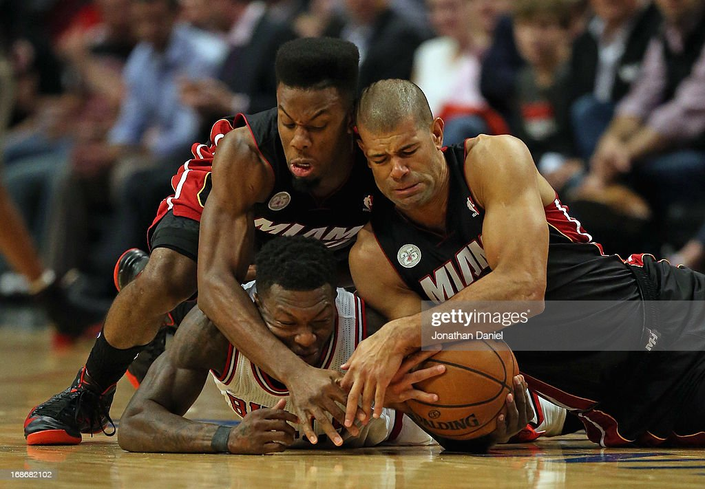 Norris Cole #30 (L) and Shane Battier #31 of the Miami Heat battle for a loose ball with Nate Robinson #2 of the Chicago Bulls in Game Four of the Eastern Conference Semifinals during the 2013 NBA Playoffs at the United Center on May 13, 2013 in Chicago, Illinois. The Heat defeated the Bulls 88-65.