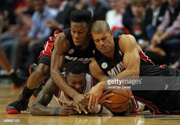 Norris Cole and Shane Battier of the Miami Heat battle for a loose ball with Nate Robinson of the Chicago Bulls in Game Four of the Eastern...