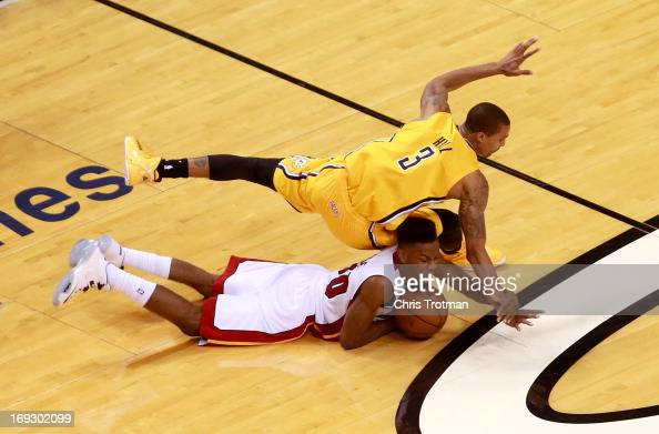 Norris Cole of the Miami Heat dives for a loose ball against George Hill of the Indiana Pacers in overtime during Game One of the Eastern Conference...