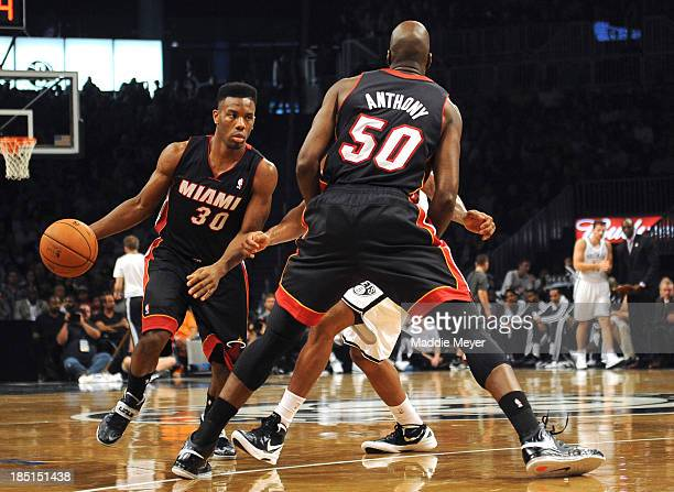 Norris Cole of the Miami Heat drives around his teammate Joel Anthony of the Miami Heat during the first quarter against the Brooklyn Nets at...