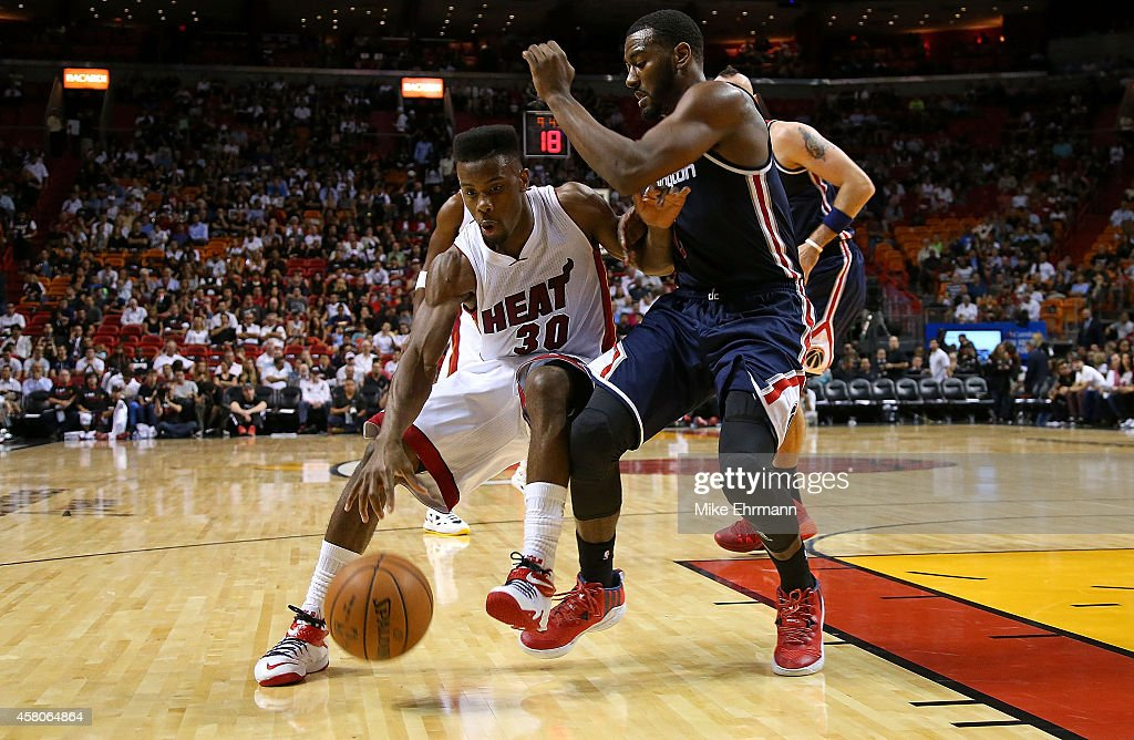 Norris Cole of the Miami Heat drives on John Wall of the Washington Wizards during the Opening night game at American Airlines Arena on October 29...