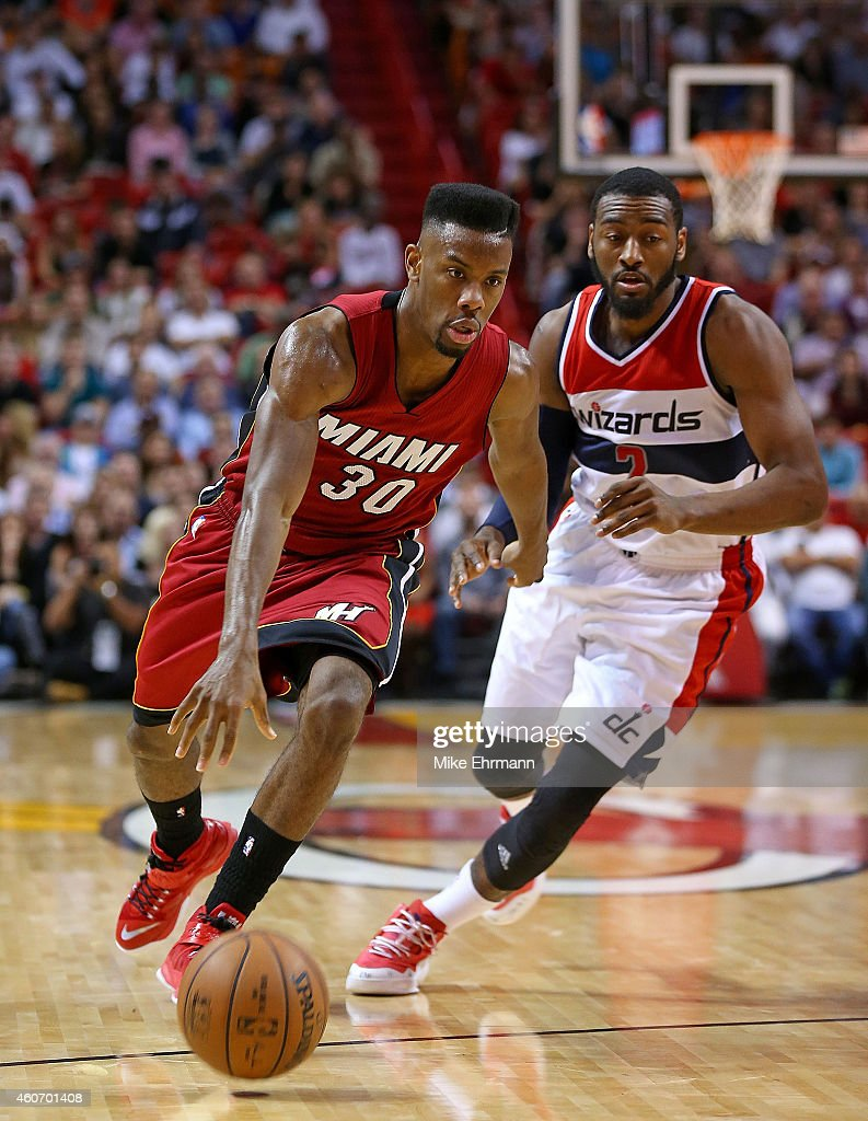 Norris Cole #30 of the Miami Heat drives on John Wall #2 of the Washington Wizards during a game at American Airlines Arena on December 19, 2014 in Miami, Florida.