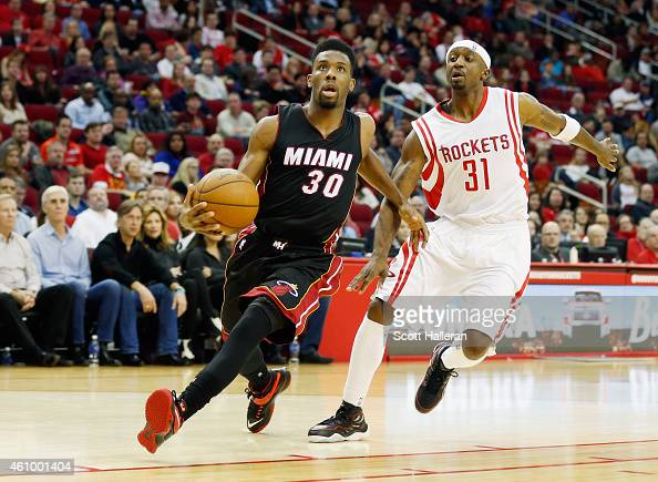 Norris Cole of the Miami Heat drives with the basketball past Jason Terry of the Houston Rockets during their game at the Toyota Center on January 3...