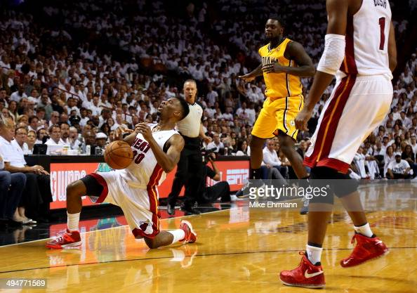 Norris Cole of the Miami Heat falls down after being hit in the face by Lance Stephenson of the Indiana Pacers during Game Six of the Eastern...