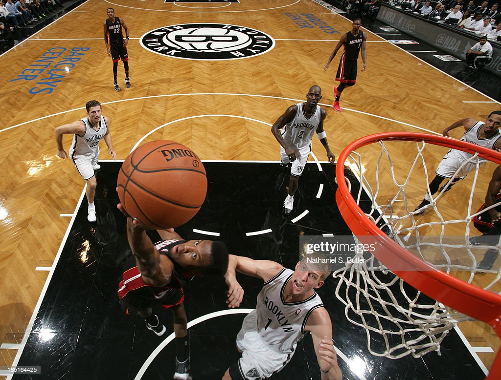 Norris Cole #30 of the Miami Heat goes up to shoot over Mason Plumlee #1 of the Brooklyn Nets during a preseason game at the Barclays Center on October 17, 2013 in the Brooklyn borough of New York City.