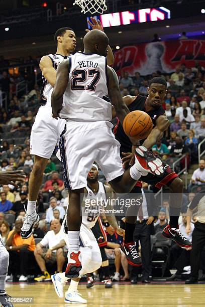 Norris Cole of the Miami Heat passes the ball in the first half as he drives against Johan Petro and Gerald Green of the New Jersey Nets at...