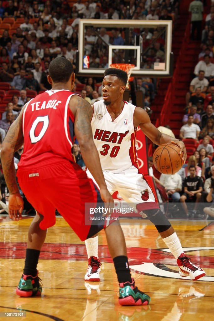 Norris Cole #30 of the Miami Heat protects the ball against Jeff Teague #0 of the Atlanta Hawks during a game between the Atlanta Hawks and the Miami Heat on December 10, 2012 at American Airlines Arena in Miami, Florida.