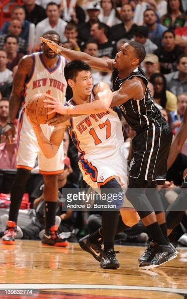 Norris Cole of the Miami Heat reaches in on Jeremy Lin of the New York Knicks for the ball during the game on February 23 2012 at American Airlines...