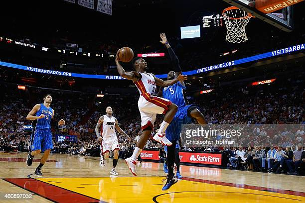 Norris Cole of the Miami Heat shoots over Victor Oladipo of the Orlando Magic at American Airlines Arena on December 29 2014 in Miami Florida NOTE TO...