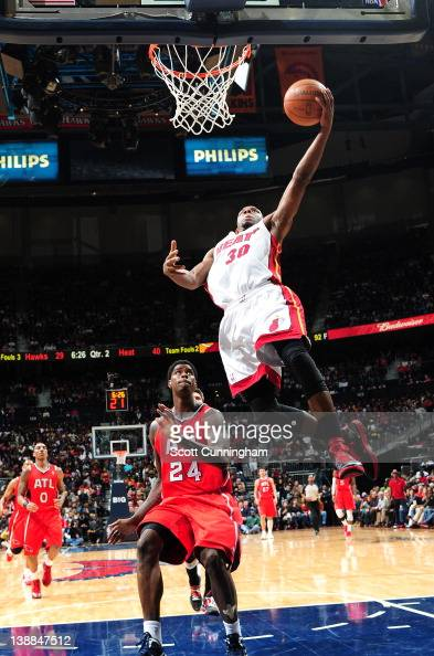 Norris Cole of the Miami Heat takes a layup against Marvin Williams of the Atlanta Hawks on February 12 2012 at Philips Arena in Atlanta Georgia NOTE...
