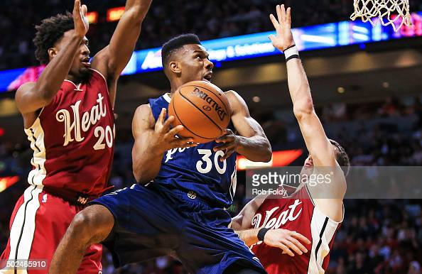 Norris Cole of the New Orleans Pelicans shoots while defended by Justise Winslow and Goran Dragic of the Miami Heat during the first half of the game...