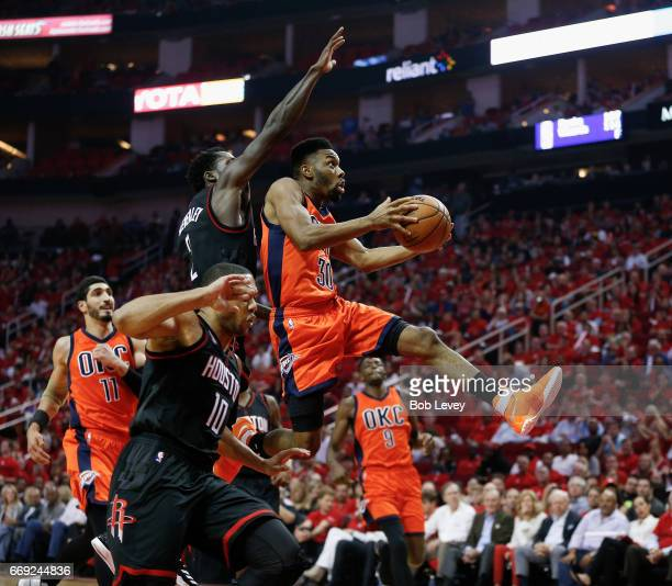 Norris Cole of the Oklahoma City Thunder drives past Patrick Beverley of the Houston Rockets for a layup during Game One of the first round of the...