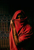 A north African woman covers her face with a veil. She is wearing wrist bangles and standing in front of a kilim rug.   Scanned from film.