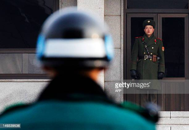A North and a South Korean soldier look at each other's sides at the Panmunjom truce village in the demilitarized zone separating the two Koreas in...