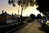 A wet suburban inner city street and parked cars after a sunset storm.