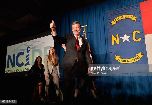 North Carolina Democratic presumptive Governor elect Roy Cooper waves to a crowd at the North Carolina Democratic Watch Party as he walks on stage...