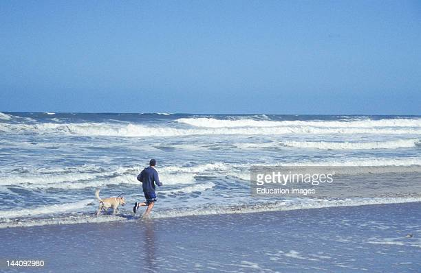North Carolina Man And Dog Running In Surf
