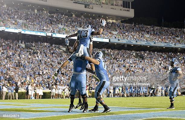 North Carolina receiver Mack Hollins celebrates with teammates after racing 33 yards to the end zone after a pass reception from quarterback Marquise...