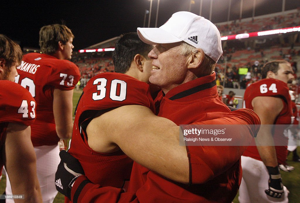 North Carolina State head coach Tom O'Brien embraces senior Brandan Bishop (30) after the Wolfpack's 27-10 victory over Boston College on Saturday, November 24, 2012, at Carter-Finley Stadium in Raleigh, North Carolina.