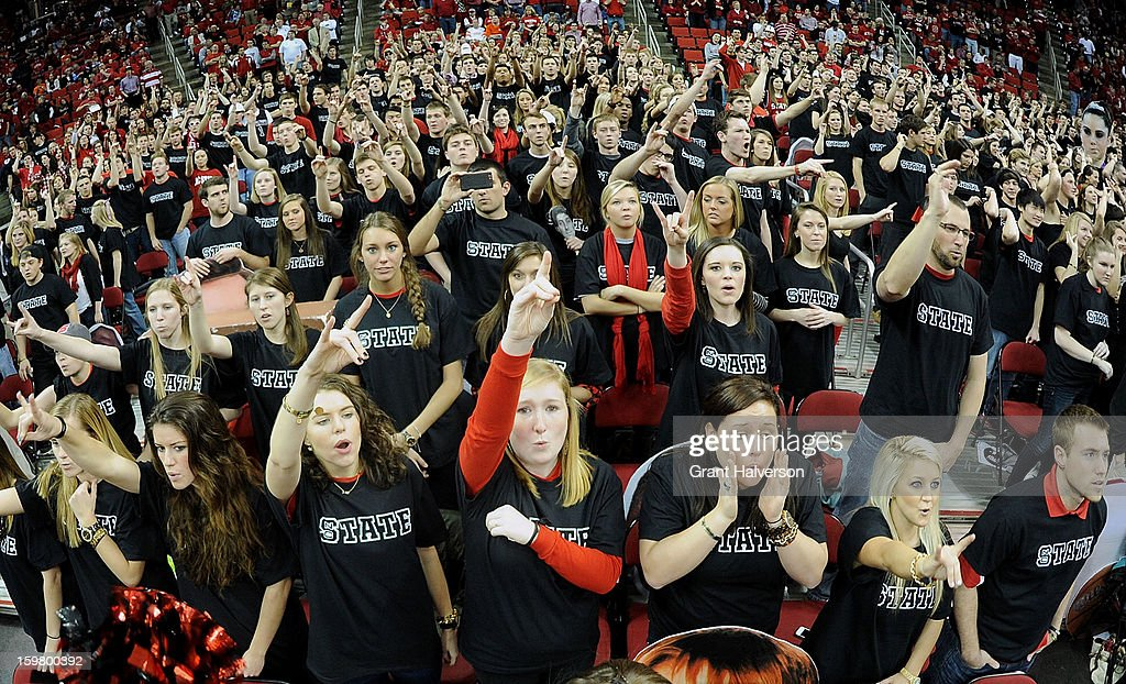 North Carolina State Wolfpack flash the 'Wolfpack' symbol as they participate in a blackout game against the Clemson Tigers during play at PNC Arena on January 20, 2013 in Raleigh, North Carolina.
