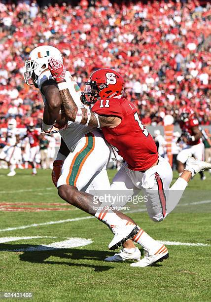 North Carolina State Wolfpack safety Josh Jones tackles Miami Hurricanes tight end Christopher Herndon IV during the first half of the game between...