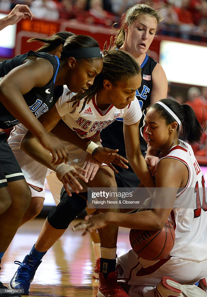 North Carolina State's Ashley Eli (10) goes to the floor as Duke's Elizabeth Williams (1) and Haley Peters (33) join teammates Lakeesa Daniel in a fight for the ball at Reynolds Coliseum in Raleigh, North Carolina, on Thursday January 3, 2013.