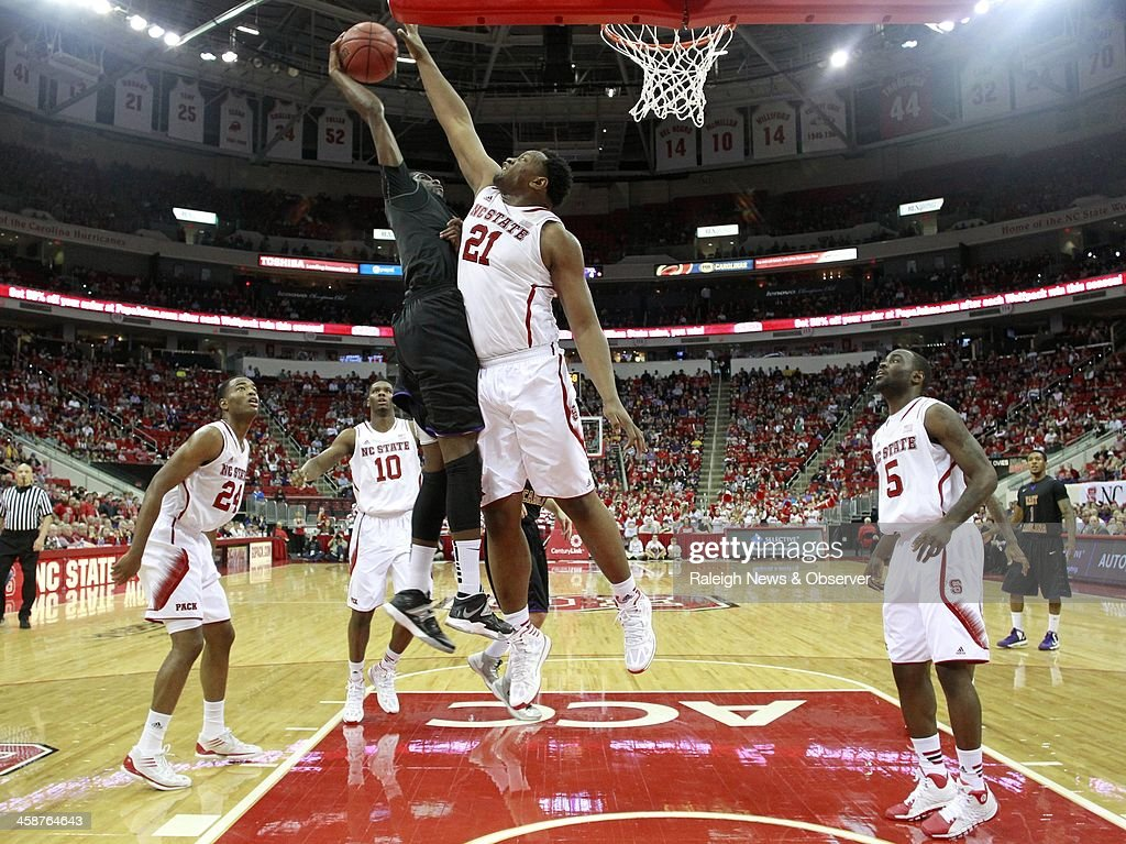 North Carolina State's Beejay Anya (21) blocks a shot by East Carolina's Prince Williams (4) in the first half at PNC Arena in Raleigh, N.C., Saturday, Dec. 21, 2013. N.C. State defeated ECU, 90-79.