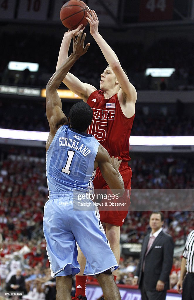 North Carolina State's Scott Wood drills a 3-pointer while being fouled by North Carolina's Dexter Strickland (1) during the second half on Saturday, January 26, 2013, at the PNC Arena in Raleigh, North Carolina. The host Wolfpack won, 91-83.