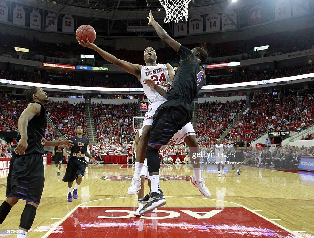 North Carolina State's T.J. Warren (24) shoots while defended by East Carolina's Prince Williams (4) in the second half at PNC Arena in Raleigh, N.C., Saturday, Dec. 21, 2013. N.C. State defeated ECU, 90-79.