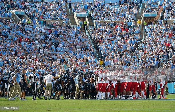 North Carolina Tar Heels and North Carolina State Wolfpack players leave their benches after a contested play during the first half of their game at...