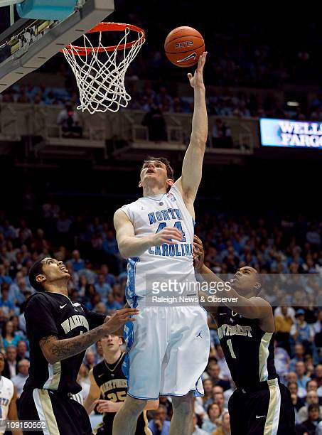 North Carolina's Tyler Zeller puts up a shot between Wake Forest's Ty Walker and Tony Chennault in the first half at the Smith Center in Chapel Hill...