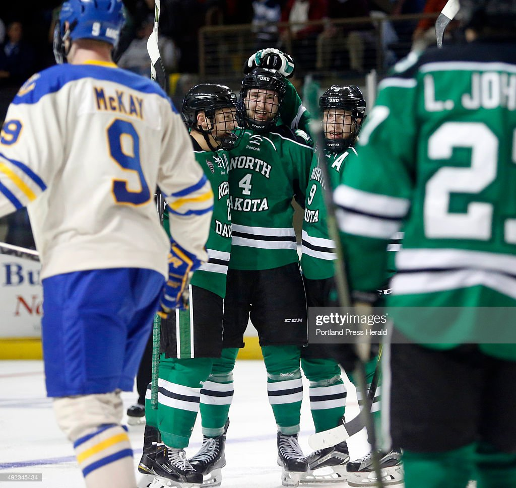 North Dakota teammates Troy Stecher and Drake Caggiula celebrate with Keaton Thompson after he tied the score at 22 during the second period in the...