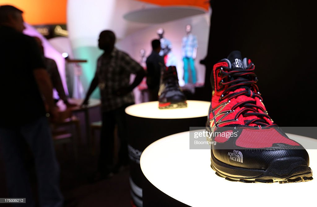 A North Face Inc. shoe sits on display while attendees visit the company's booth during the Outdoor Retailer Summer Market show in Salt Lake City, Utah, U.S., on Thursday, Aug. 1, 2013. Consumer spending in the U.S. rose in line with forecasts in June as Americans' incomes grew, a sign the biggest part of the economy is withstanding fiscal headwinds. Photographer: George Frey/Bloomberg via Getty Images