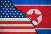 north korea flag on broken brick wall and half usa united states of america flag, crisis trump president and north korean for nuclear atomic bomb risk war concept
