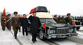 PYONGYANG North Korea Kim Jong Un son of the late North Korean leader Kim Jong Il and his successor salutes as he walks beside the hearse carrying...