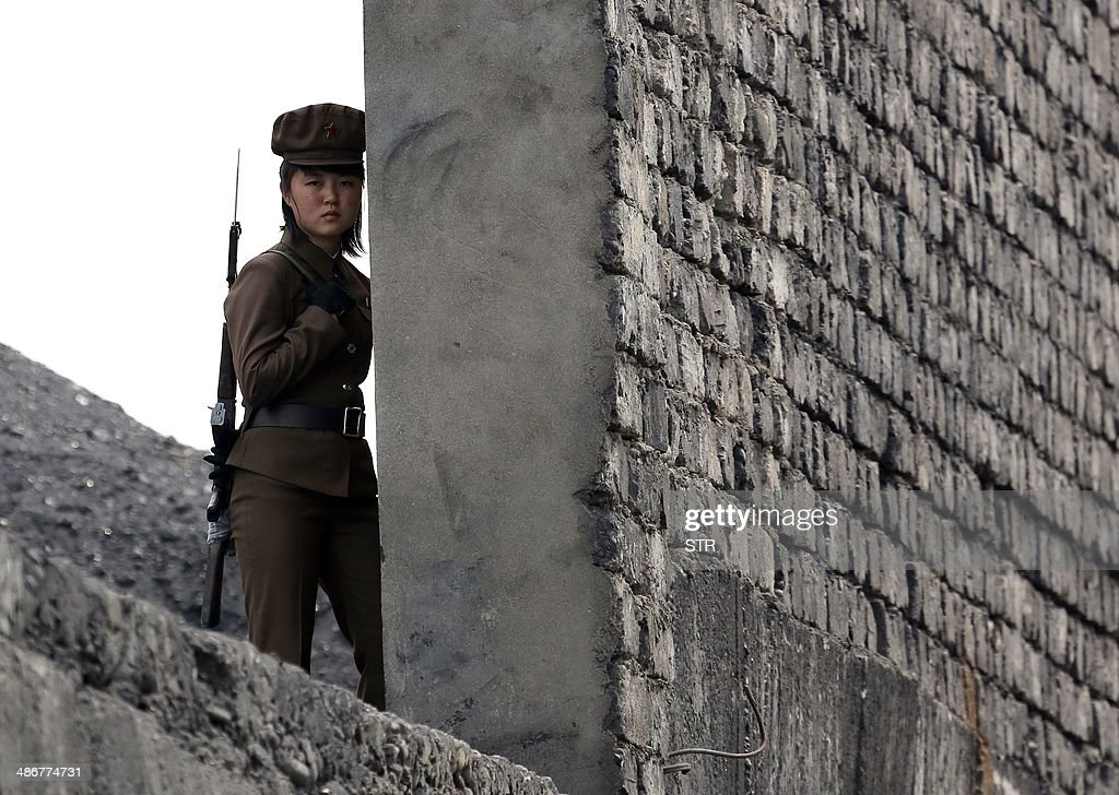 A North Korea woman soldier patrols the bank of the Yalu River which separates the North Korean town of Sinuiju from the Chinese border town of...