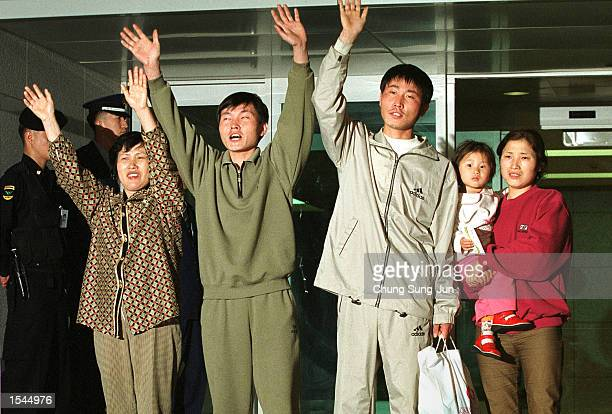 North Korean asylum seekers and their relatives who escaped from North Korea last June and live in Seoul wave to the news media upon on their arrival...