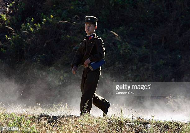 North Korean border guard walks on the banks of the Yalu River opposite the Chinese border city of Dandong on October 17 2006 in Uiju Democratic...