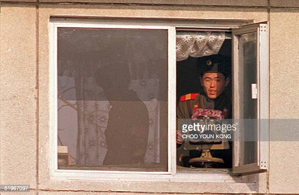 North Korean border guard with powerful binoculars watches the southern side of the treaty village of Panmunjom from a watchtower 20 December 1994 At...