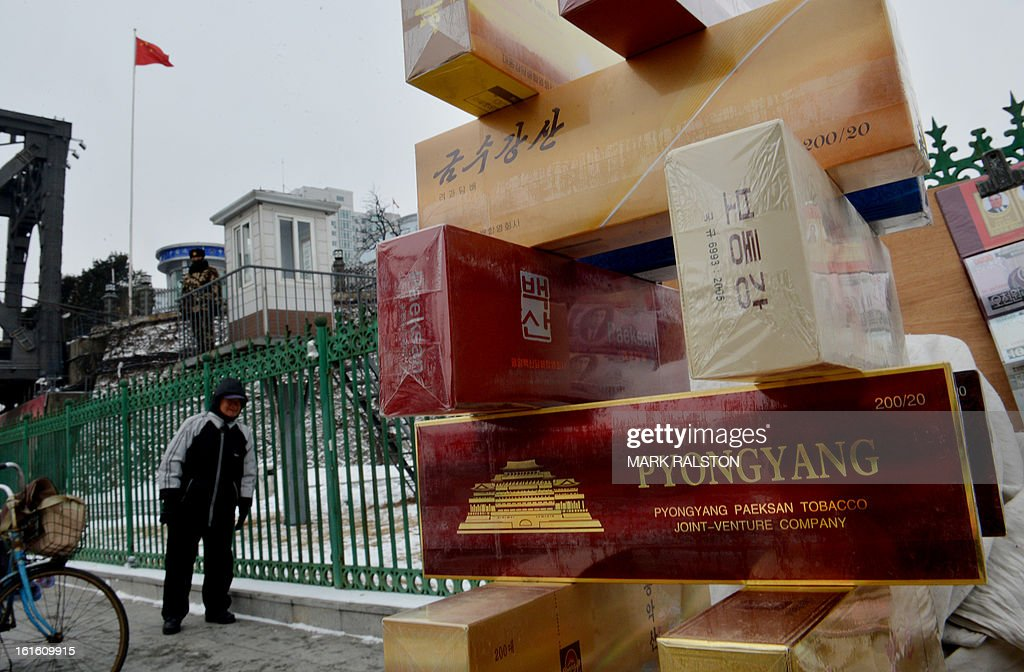 North Korean cigarettes for sale beside a Chinese para-military officer who keeps watch on the Sino-Korean Friendship Bridge linking the North Korean town of Sinuiju with the Chinese city of Dandong, on February 13, 2013. While the rest of the world reacted with outrage, North Koreans were swept up in a 'storm of excitement' over their country's latest nuclear test, state media reported. The countries third nuclear test was widely condemned by the international community, led by the United States and the UN Security Council, which met in emergency session the same day. AFP PHOTO/Mark RALSTON