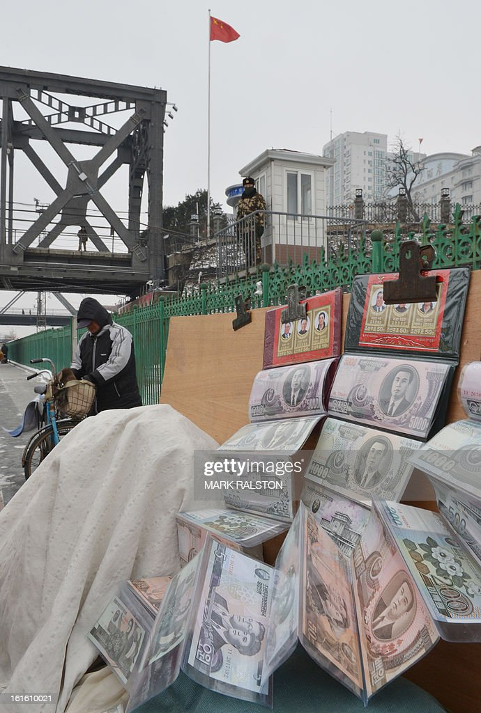 North Korean currency for sale at a tourist stall beside a Chinese para-military officer who keeps watch on the Sino-Korean Friendship Bridge linking the North Korean town of Sinuiju with the Chinese city of Dandong, on February 13, 2013. While the rest of the world reacted with outrage, North Koreans were swept up in a 'storm of excitement' over their country's latest nuclear test, state media reported. The countries third nuclear test was widely condemned by the international community, led by the United States and the UN Security Council, which met in emergency session the same day. AFP PHOTO/Mark RALSTON